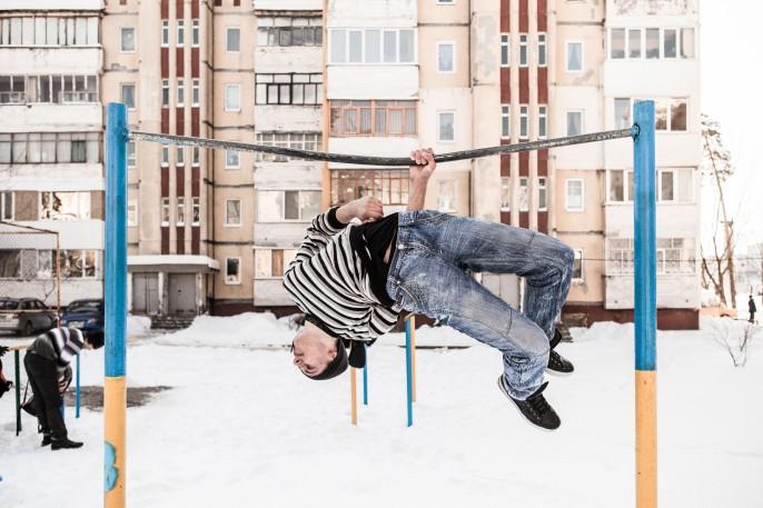 Un jeune homme fait une acrobatie dans une aire de jeu. Crédit : Niels Ackermann.